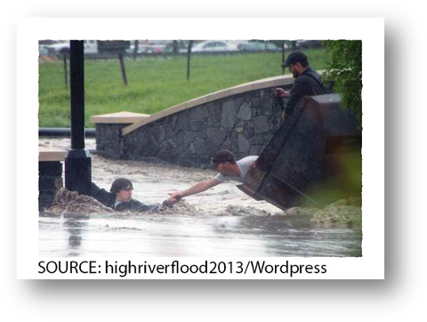 Photo of an individual helping a resident from being swept away by flood waters.
