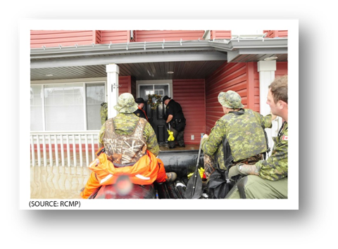 Photo of locksmiths opening the door of an evacuated house in the Town of High River.